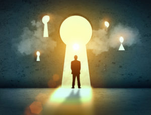 Silhouette of businessman standing in keyhole sun shining above